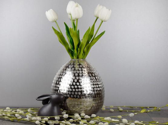 Metallvase mit schönen Kunsttulpen und Keramikosterhase