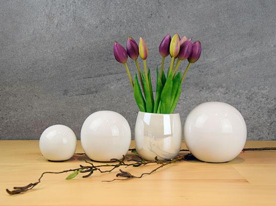Weiße Keramikkugeln in drei Größen mit weißer Glasvase und Kunsttulpen