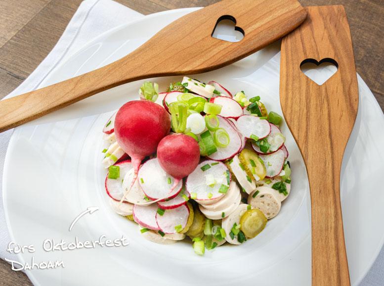 Weißwurstsalat zubereitet und serviert mit Holzkochlöffeln